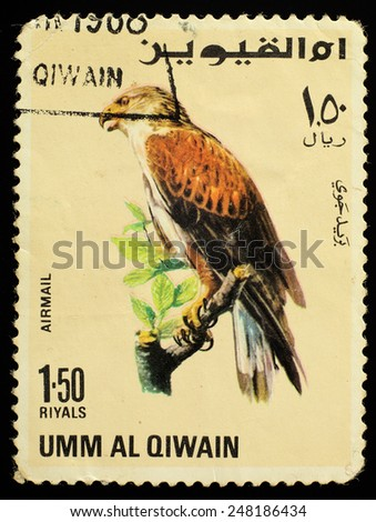 Emirate of Umm al-Quwain  - CIRCA 1968: Postage stamp printed in Umm al-Quwain showing a bird of prey - Falcon, circa 1968. - stock photo
