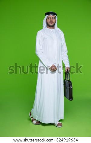 Emirati businessman carrying bag - stock photo