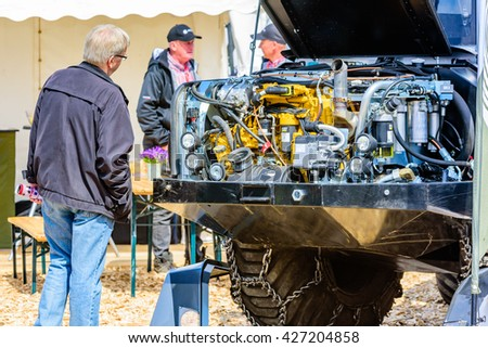 Emmaboda, Sweden - May 14, 2016: Forest and tractor (Skog och traktor) fair. Malwa forwarder with open hood and visible motor. Person looking at motor.