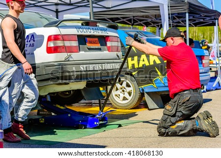 Emmaboda, Sweden - May 7, 2016: 41st South Swedish Rally in service depot. Crew member at team Berglund (13) rigs a hydraulic garage jack under their Volvo 940.