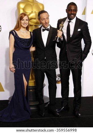 Emmanuel Lubezki, Jessica Chastain and Idris Elba at the 87th Annual Academy Awards - Press Room held at the Loews Hollywood Hotel in Los Angeles, USA February 22, 2015. - stock photo