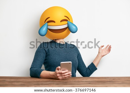Emoji Head Woman sitting at the desk. Woman wearing tears of joy emoji masks while looking at her phone. This emoji is laughing so much that it is crying tears of joy