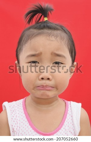 Emoticon face (sad) of asian kid on isolated red background - stock photo