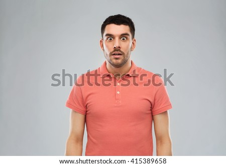 emotion, advertisement and people concept - surprised man in polo t-shirt over gray background - stock photo