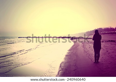 Emotion conceptual image. Lonely woman walking on the beach. Instagram vintage picture. - stock photo