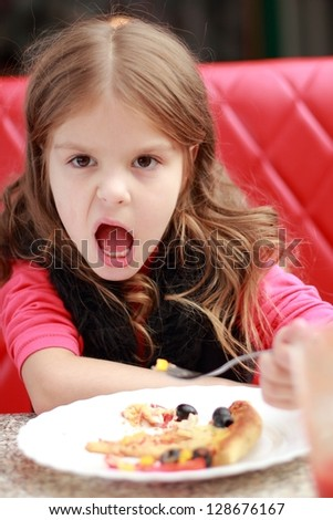 Emotion little girl eating and drinking juice in cafe