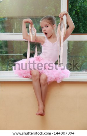 Emotion young dancer in a pink leotard has been training in ballet class - stock photo