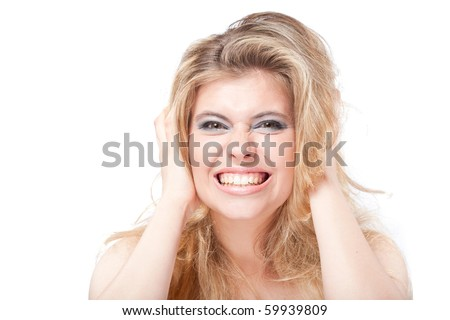 Emotional angry blonde woman showing teeth holding head with hands