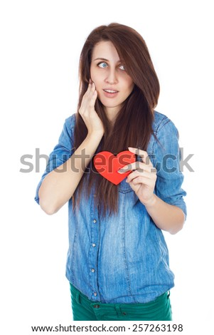 Emotional attractive brunette woman in love. Beautiful young girl in denim blue shirt standing on a white background with a red paper heart in hands.