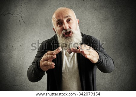 emotional bearded man screaming, stretching his hands to camera and want to smother someone over grey wall - stock photo