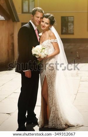 Emotional beautiful brunette bride with bouquet and handsome groom posing in city street