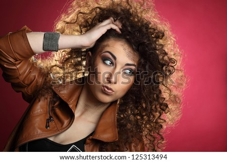 emotional beautiful girl with curly hair on pink background