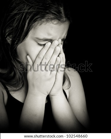 Emotional black and white portrait of a girl crying isolated on black with space for text - stock photo