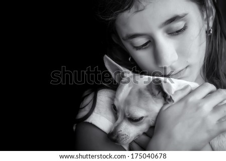 Emotional black and white portrait of a sad lonely girl hugging her small dog - stock photo