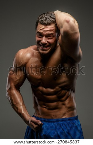 Emotional bodybuilder posing in studio. Isolated on grey