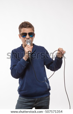 Emotional boy brunette in sunglasses with a microphone on a white background