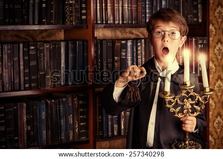 Emotional boy stands with a bunch of old keys and candles in the library with many old books. Fairy tales. Vintage style. - stock photo