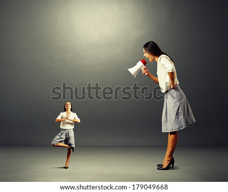 emotional businesswoman screaming at small yoga woman over dark background - stock photo