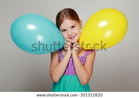 Emotional cheerful girl in a bright summer sundress holding balloons - stock photo