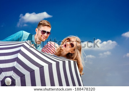 Emotional couple hiding behind the umbrella and having fun on the blue sky background - stock photo