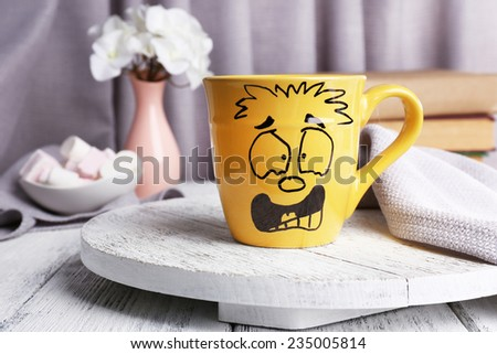 Emotional cup on wooden table - stock photo