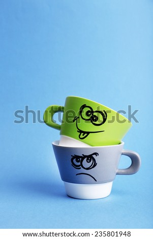 Emotional cups on blue background - stock photo