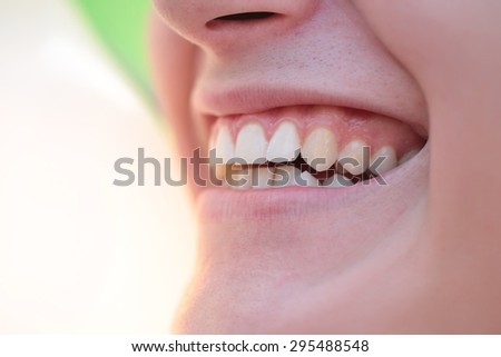 Emotional female with beautiful clear white open mouth smile of young woman with clean healthy teeth and soft tempting lips closeup, horizontal picture - stock photo