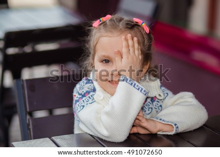 Emotional girl at a table in a cafe. Cute little girl sitting in outdoor restaurant on summer day. child in a cafe waiting for his order.