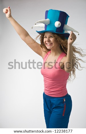 emotional girl in big football fan hat on gray background