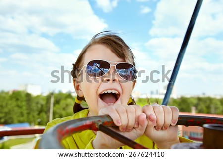 emotional girl in sunglasses in the amusement park. children outdoors. vacation in the summer park - stock photo