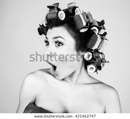Emotional girl with hair-curlers on her head. Black-white studio photo.