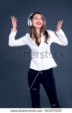 Emotional girl with headphones on a blue background. Young woman listening to music. She is happy and enjoying it. - stock photo