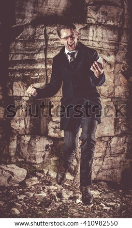 Emotional jumping businessman on the night rocks background.