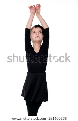 Emotional little ballerina in black tutu dancing like a black swangirl isolated over white background