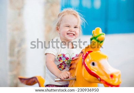Emotional little girl riding on the carousel - stock photo