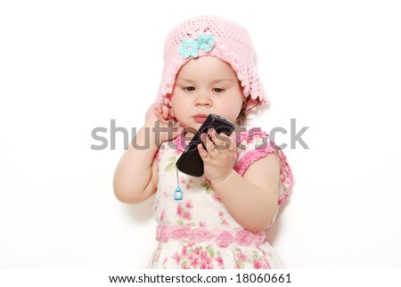 Emotional look of the baby with a mobile phone