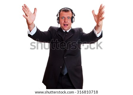 Emotional man in a business suit and wearing headphones on an isolated background - stock photo