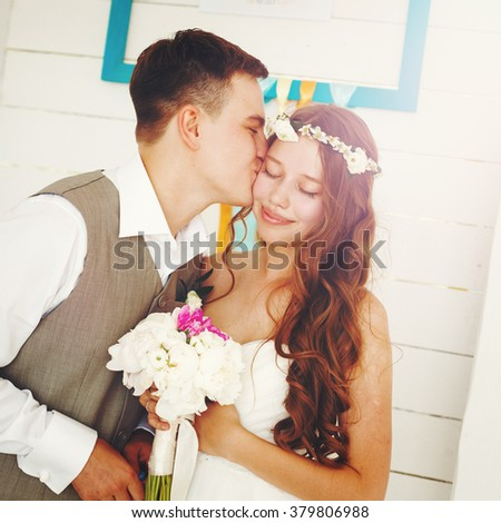 Emotional Moment of Wedding Day. Beautiful Newlywed Couple. Groom Kissing His Bride. Image Toned with Vintage Colors. - stock photo