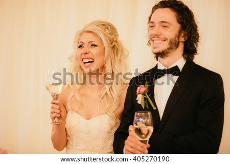 Emotional newlywed couple holding champagne glasses at wedding reception