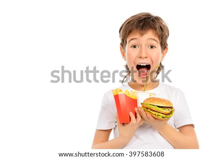 Emotional nine year old boy holds french fries, burger and soda and shouting. Fast food. Concept of healthy and unhealthy food. Isolated over white. - stock photo