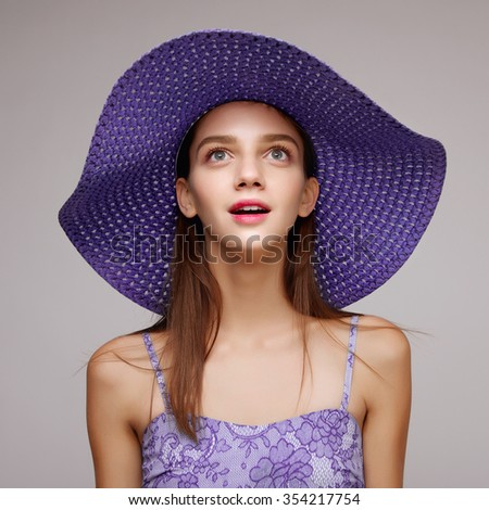 Emotional portrait of a beautiful cute girl in a lilac hat