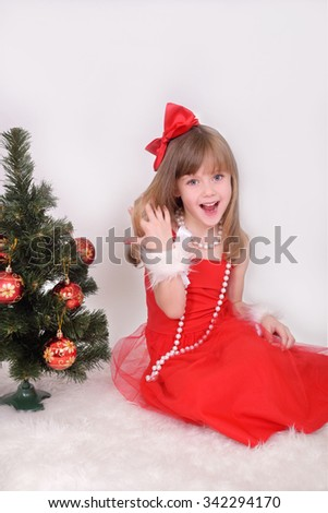 Emotional portrait of a cheerful girl in red dress.  - stock photo