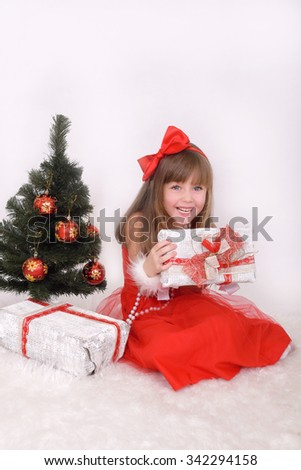 Emotional portrait of a cheerful girl in red dress. On New Year's gift in hands - stock photo
