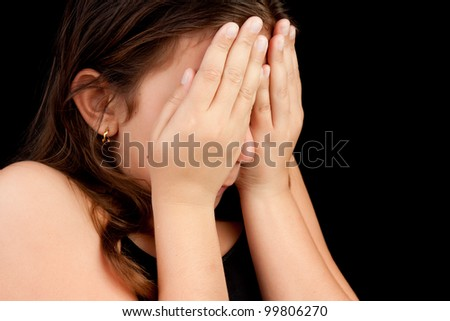 Emotional portrait of a girl crying and hiding her face isolated on black with space for text