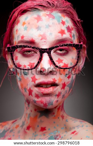 Emotional portrait of a young sensual woman with stars on the face and painted hair in pink   wearing glasses - stock photo