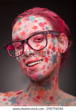 Emotional portrait of a young smiling woman with stars on the face and painted hair in pink   wearing glasses - stock photo