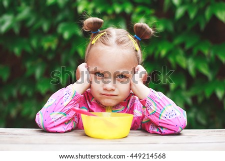 Emotional portrait of cute little toddler girl eating with spoon outdoors. - stock photo