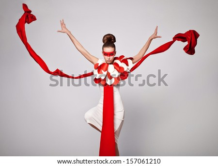 emotional portrait of fashion woman in exclusive dress posing in studio , textile is flying - stock photo