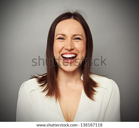 emotional portrait of happy and laughing woman over grey background - stock photo