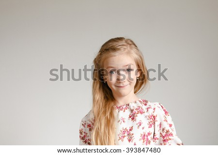 Emotional portrait of little girl with long blond hair wearing a blouse with floral print